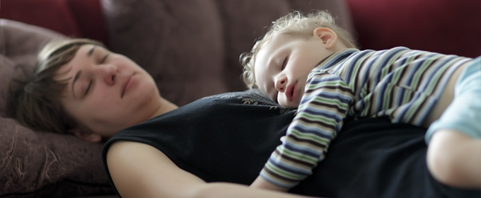 Mother and toddler resting peacefully on a couch